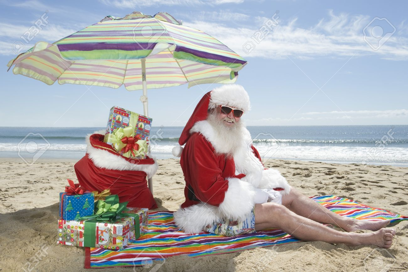 Father Christmas Sits Under A Parasol On The Beach Stock Photo ...