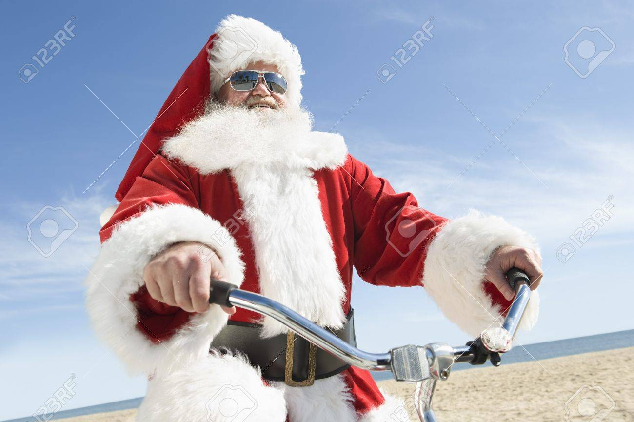 Father Christmas cycles along beach front Stock Photo - 12738136