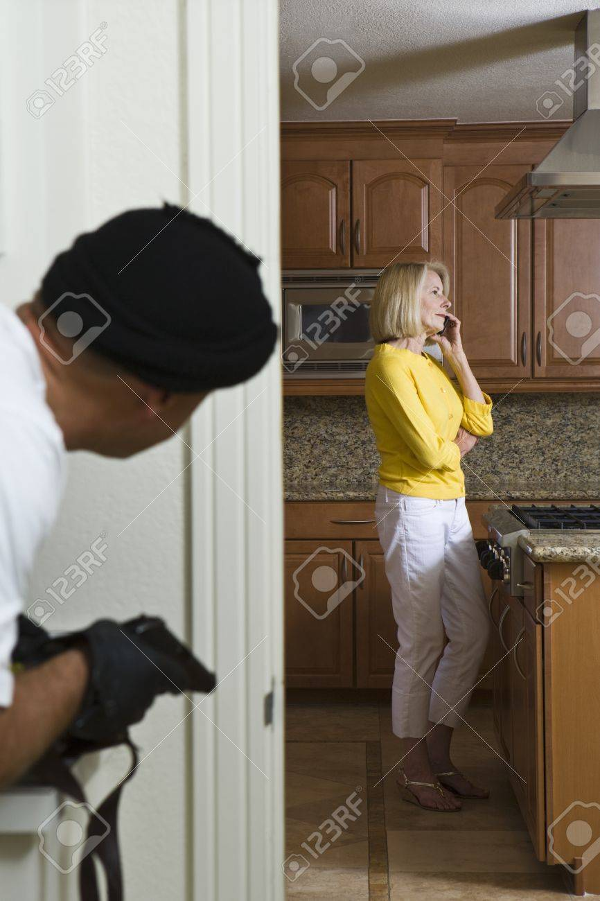 Burglar holding gun approaches woman on phone in kitchen Stock Photo - 12738146