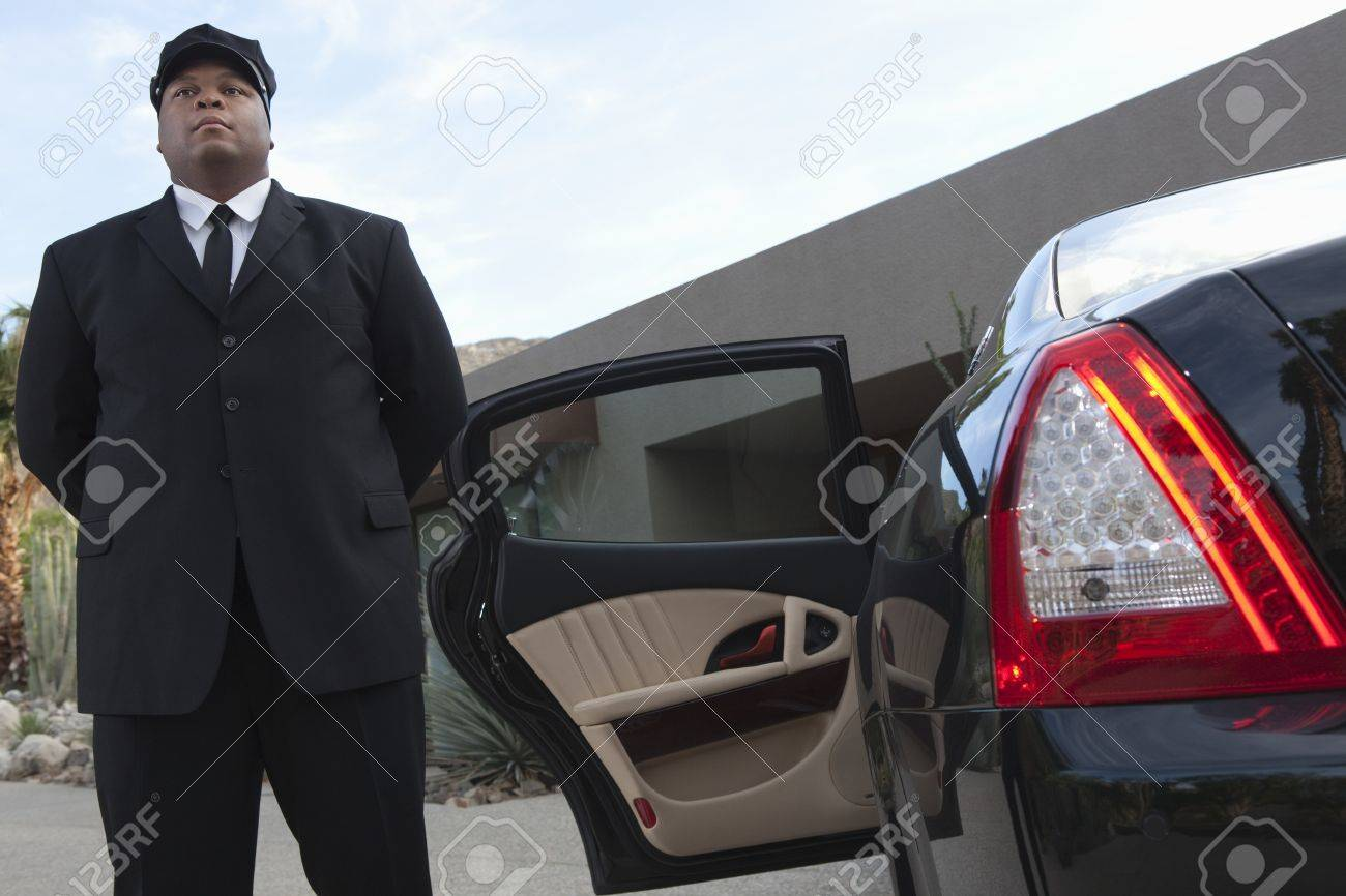 Chauffeur Stands At Open Car Door Of Luxury Vehicle Stock Photo