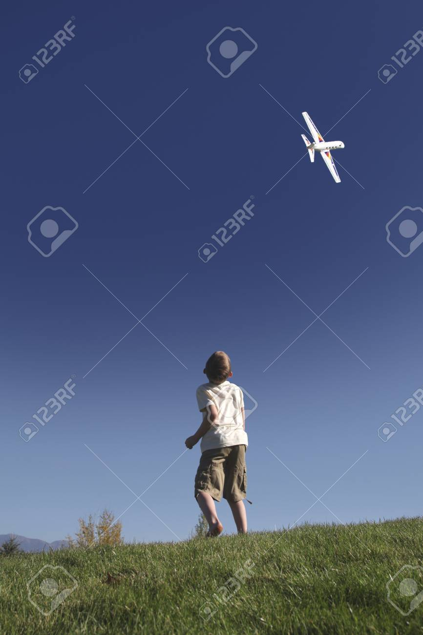 Boy stands on hilltop flying model plane Stock Photo - 12738365