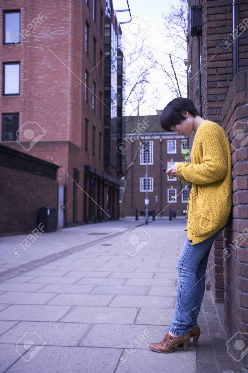 A young female adult using her phone while leaning on the wall Stock Photo - 12738440