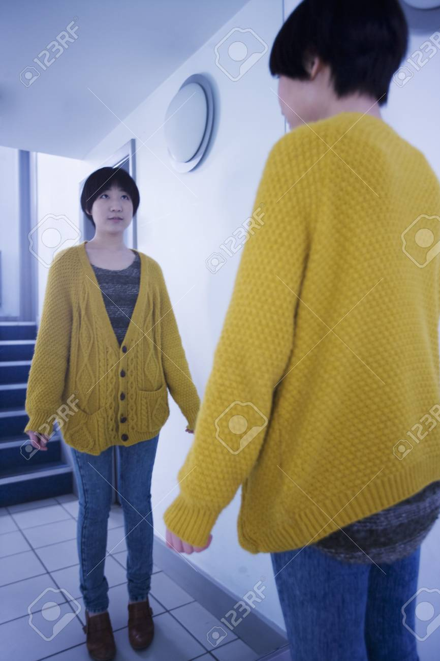 A female adult standing and looking into the mirror Stock Photo - 12738447