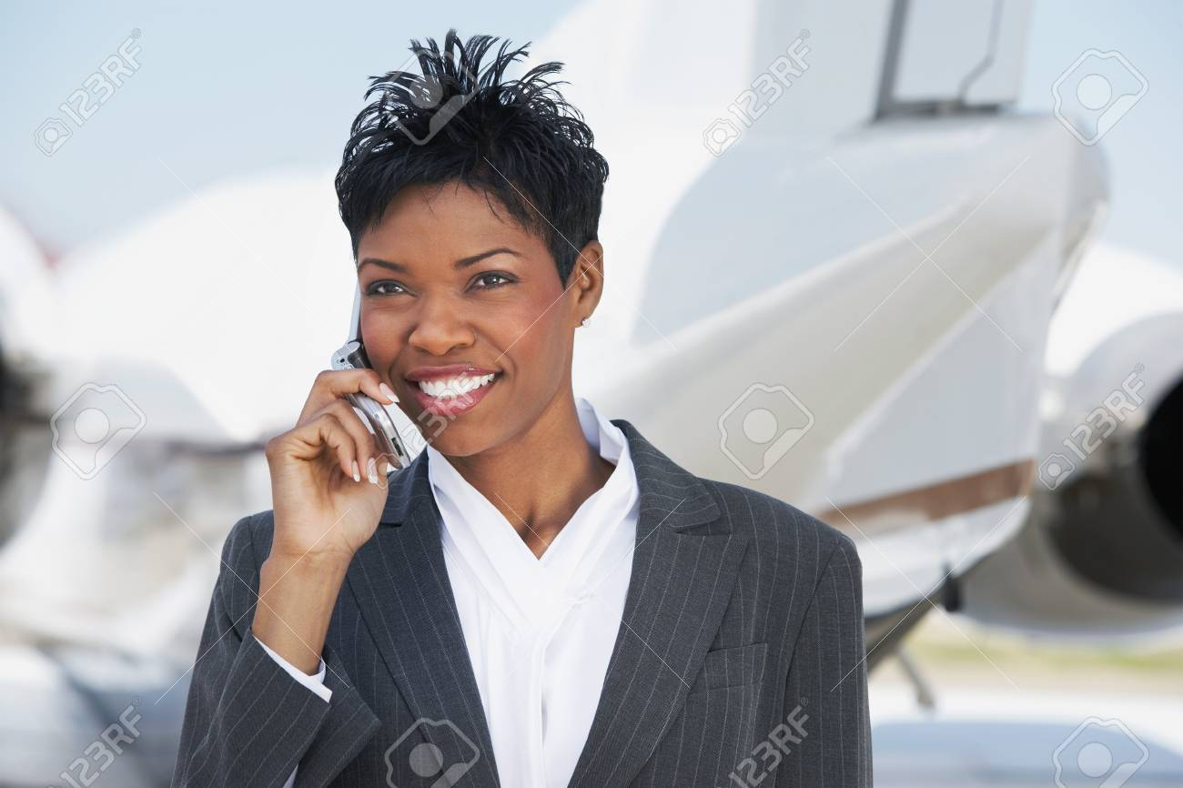 Smiling Businesswoman standing outside Airplane talking on mobile Stock Photo - 18884274