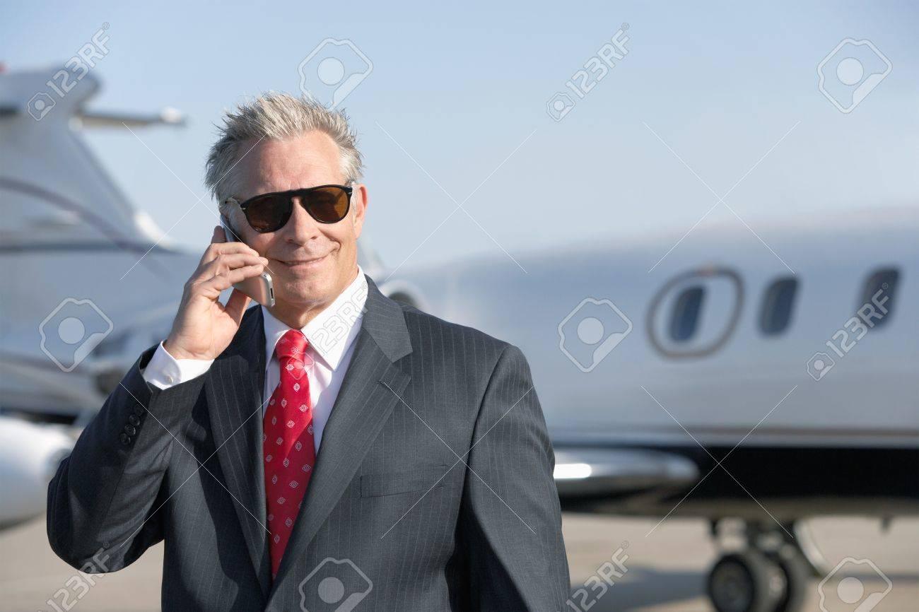 Businessman standing on landing strip near private jet talking on mobile Stock Photo - 19045627