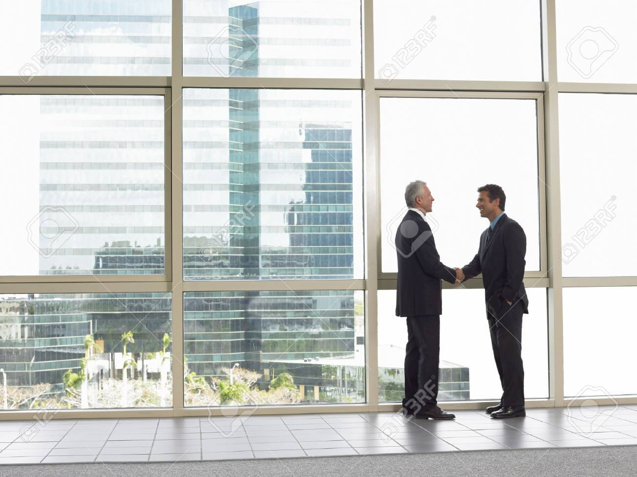 Businessmen shaking hands in office building Stock Photo - 18884624