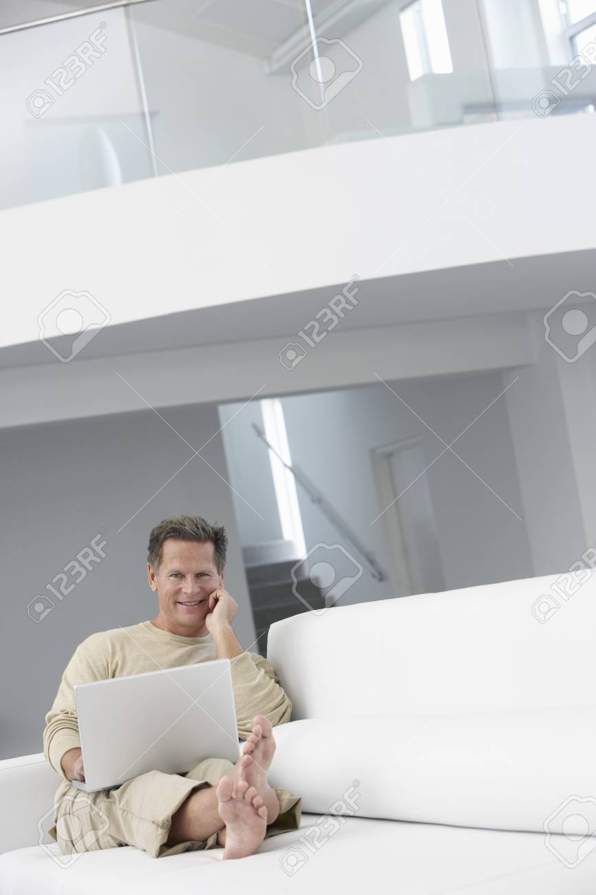 Man using laptop on sofa in living room Stock Photo - 19075559