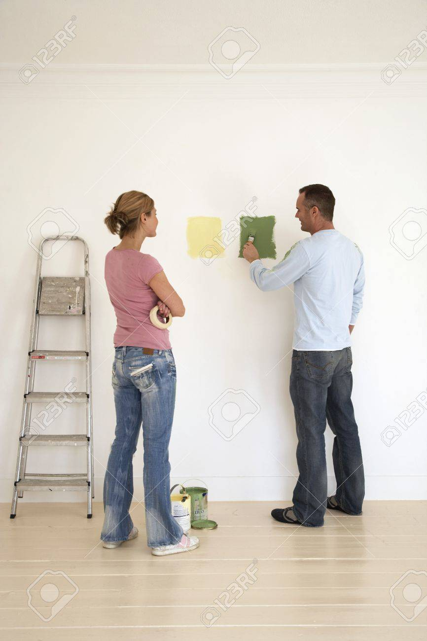 Woman Watching Man Testing Paint Colours On Wall Stock Photo