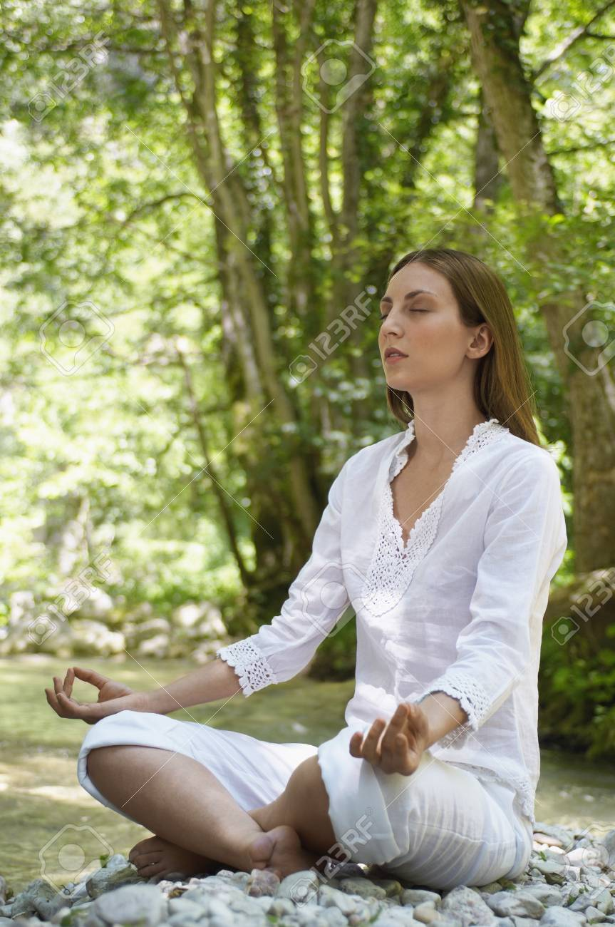 Young woman meditating by forest river, full length Stock Photo - 18886502