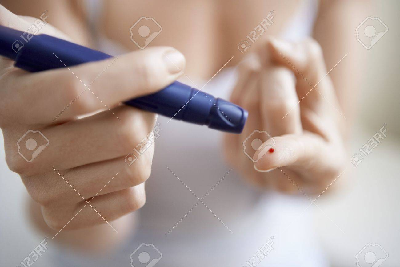 Woman using lancelet on finger mid-section close up of finger Stock Photo - 19075853