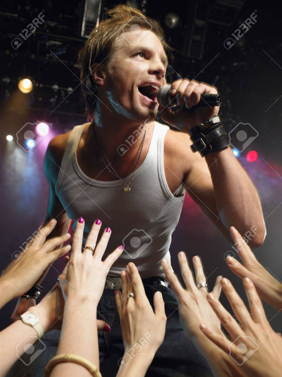 Low angle view of male rock star singing on stage with adoring fans reaching their hands up towards him Stock Photo - 19326908