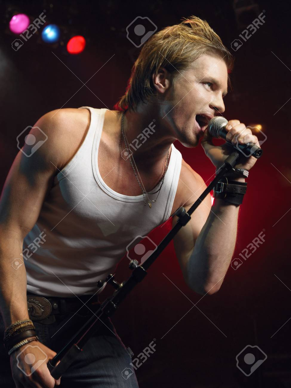 Young Man Singing into microphone on stage at Concert low angle view Stock Photo - 19326923