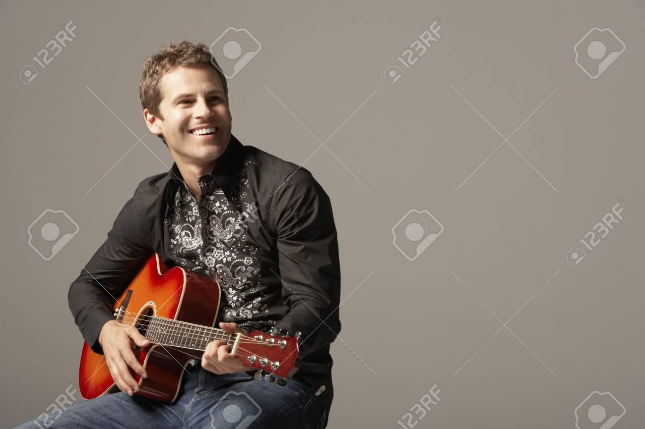 Man sitting Playing Guitar smiling Stock Photo - 19108259