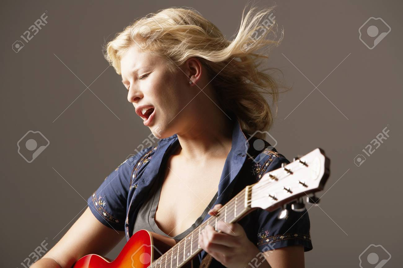 Woman Playing Guitar and Singing Stock Photo - 18886194