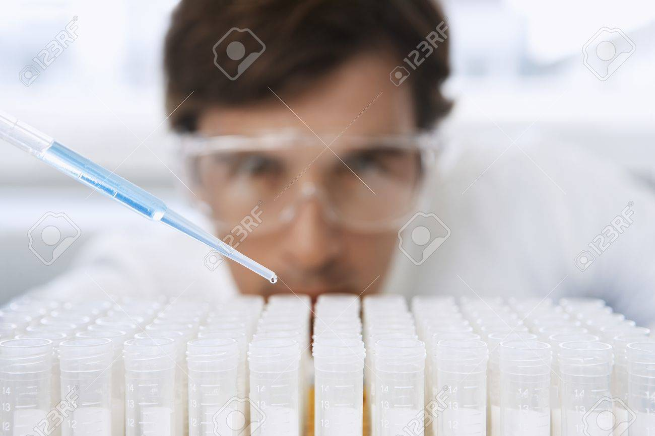 Lab Worker Adding Liquid to Test Tubes Stock Photo - 18885254