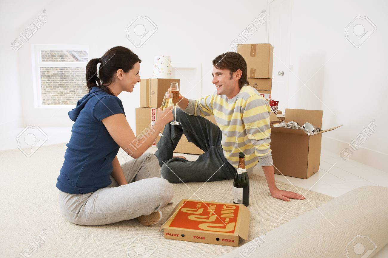 Couple in new home toasting with champagne and pizza Stock Photo - 19213660