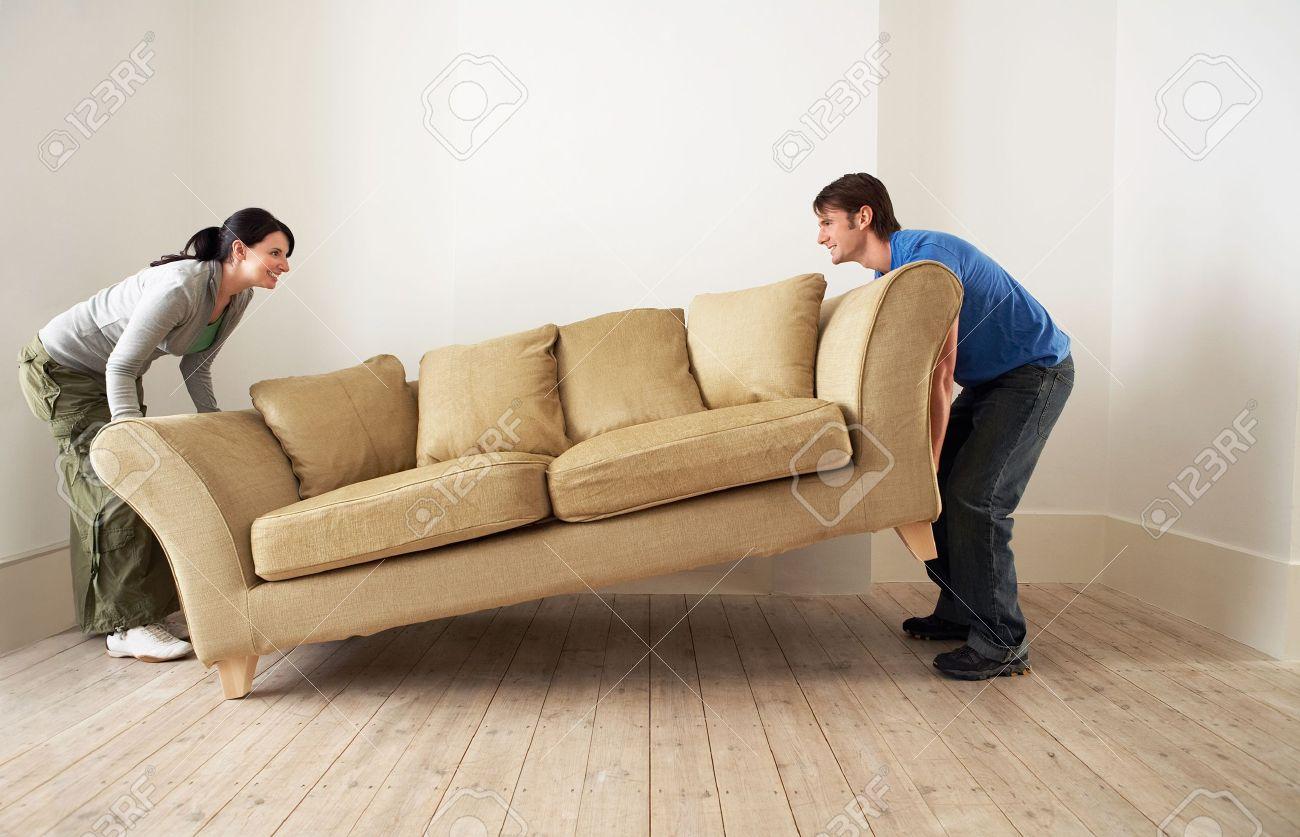 Couple lifting sofa in empty room Stock Photo - 19326889