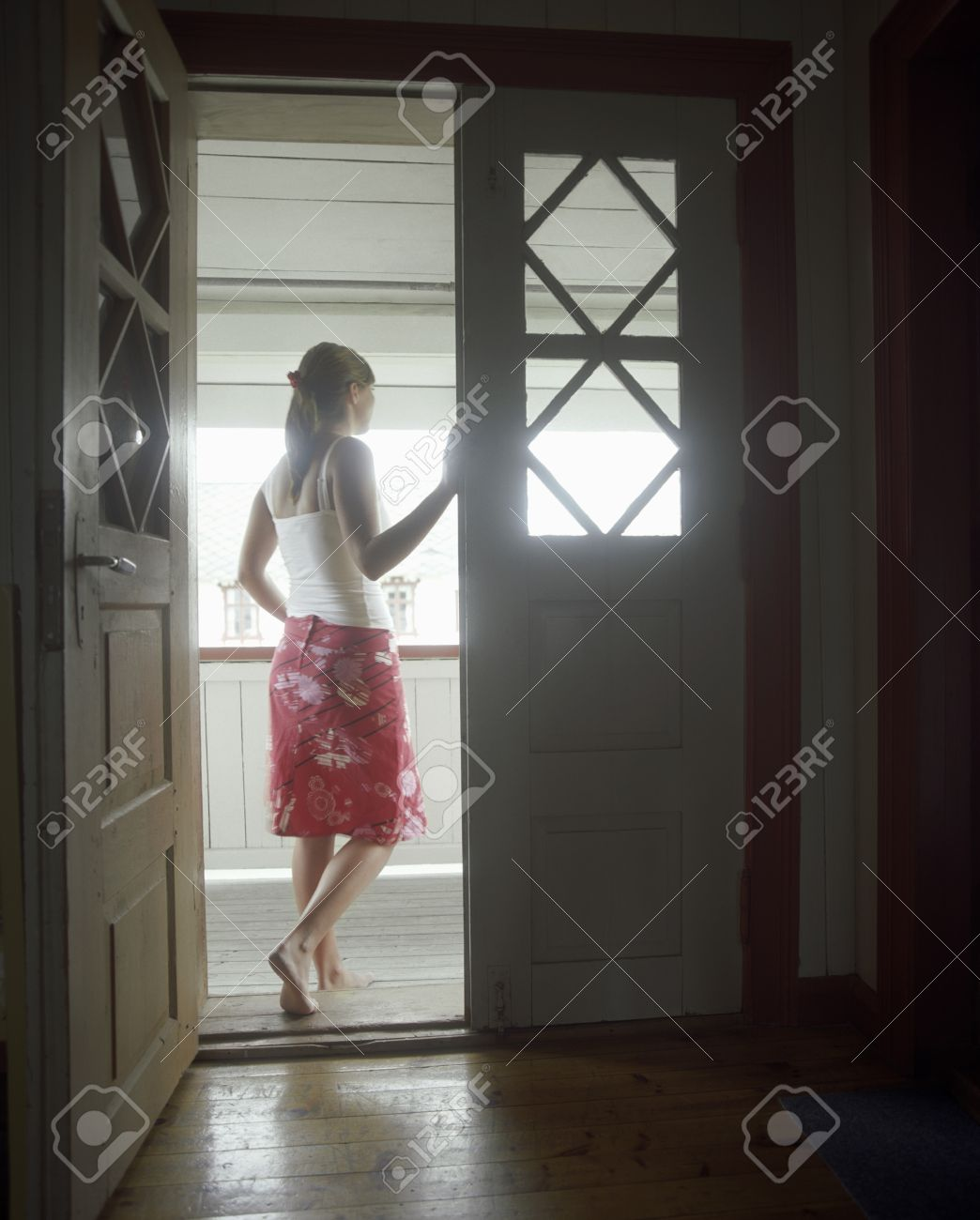 looking out door. Stock Photo - Woman Standing In Open Door Looking Out Back View K