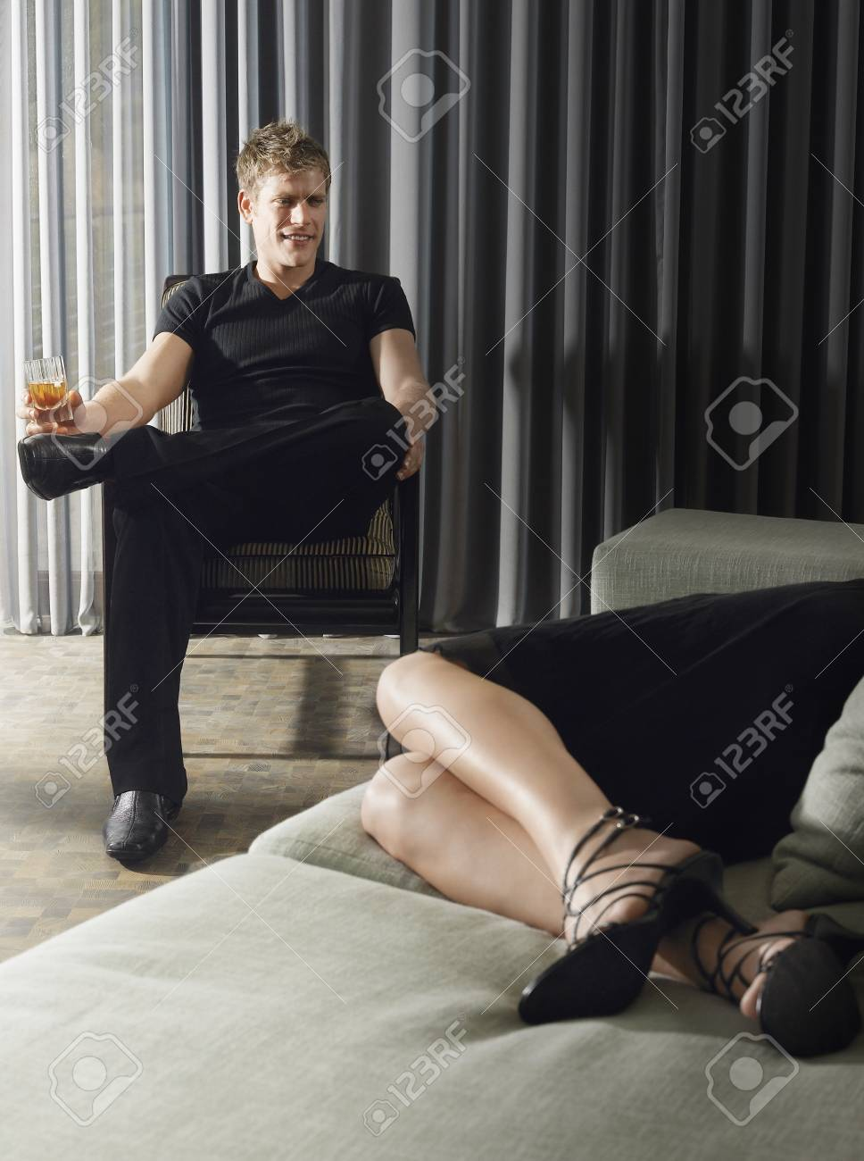 Man sitting with an alcoholic drink with woman reclining on sofa in living room Stock Photo - 18898568