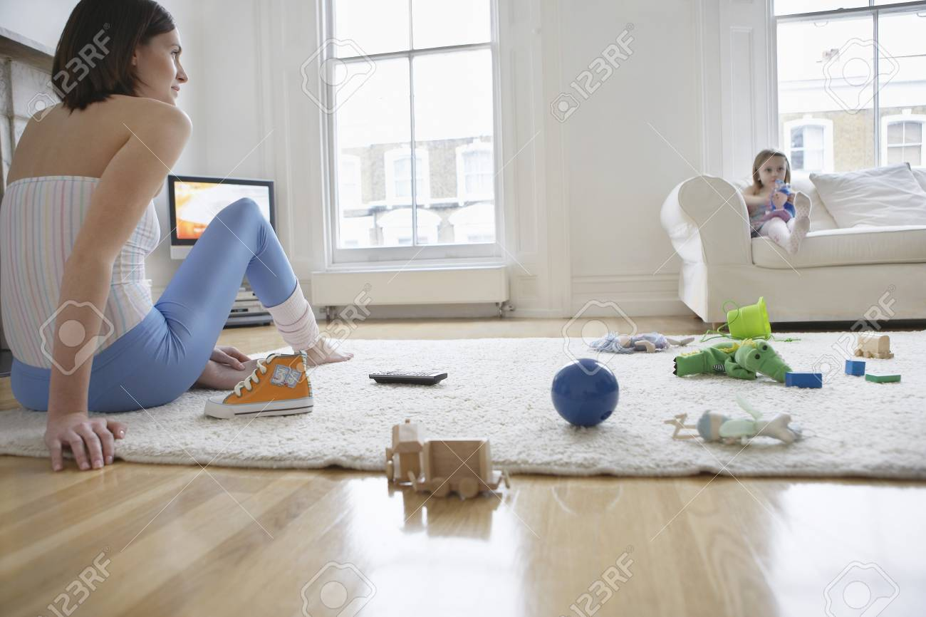 Mother And Daughter Watching Television In Messy Living Room Stock ...