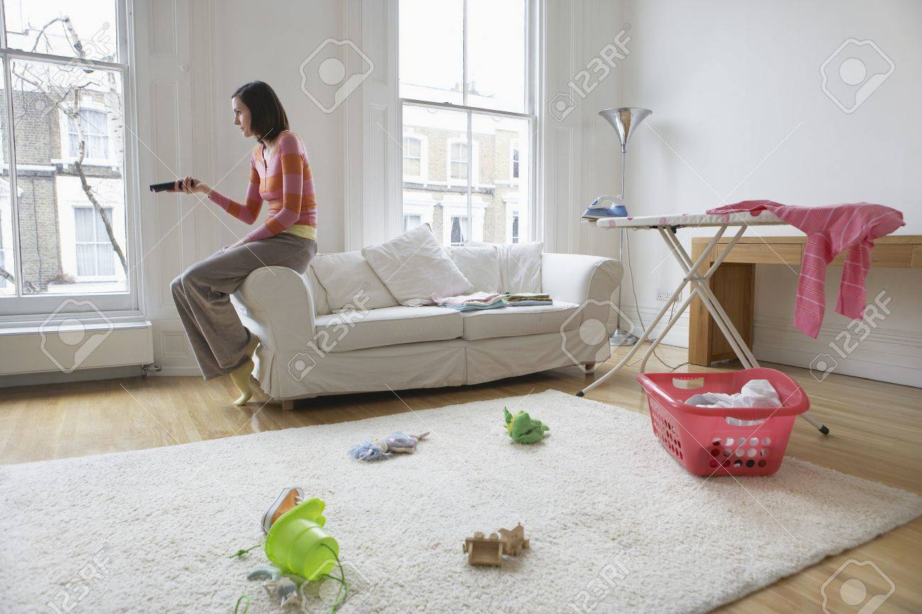 Housewife Watching Television In Messy Living Room Stock Photo ...