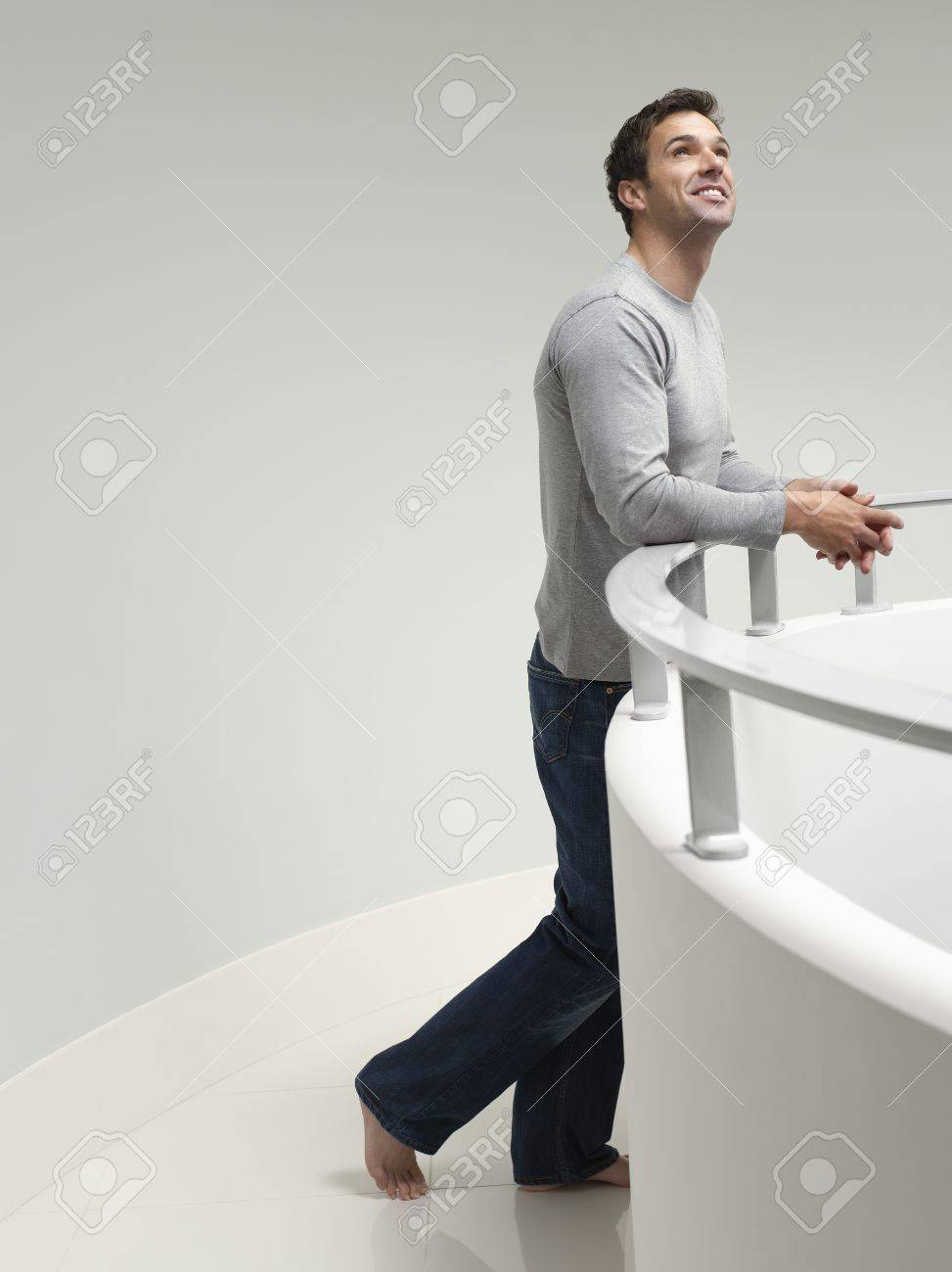 young man leaning on railing indoors looking up stock photo picture