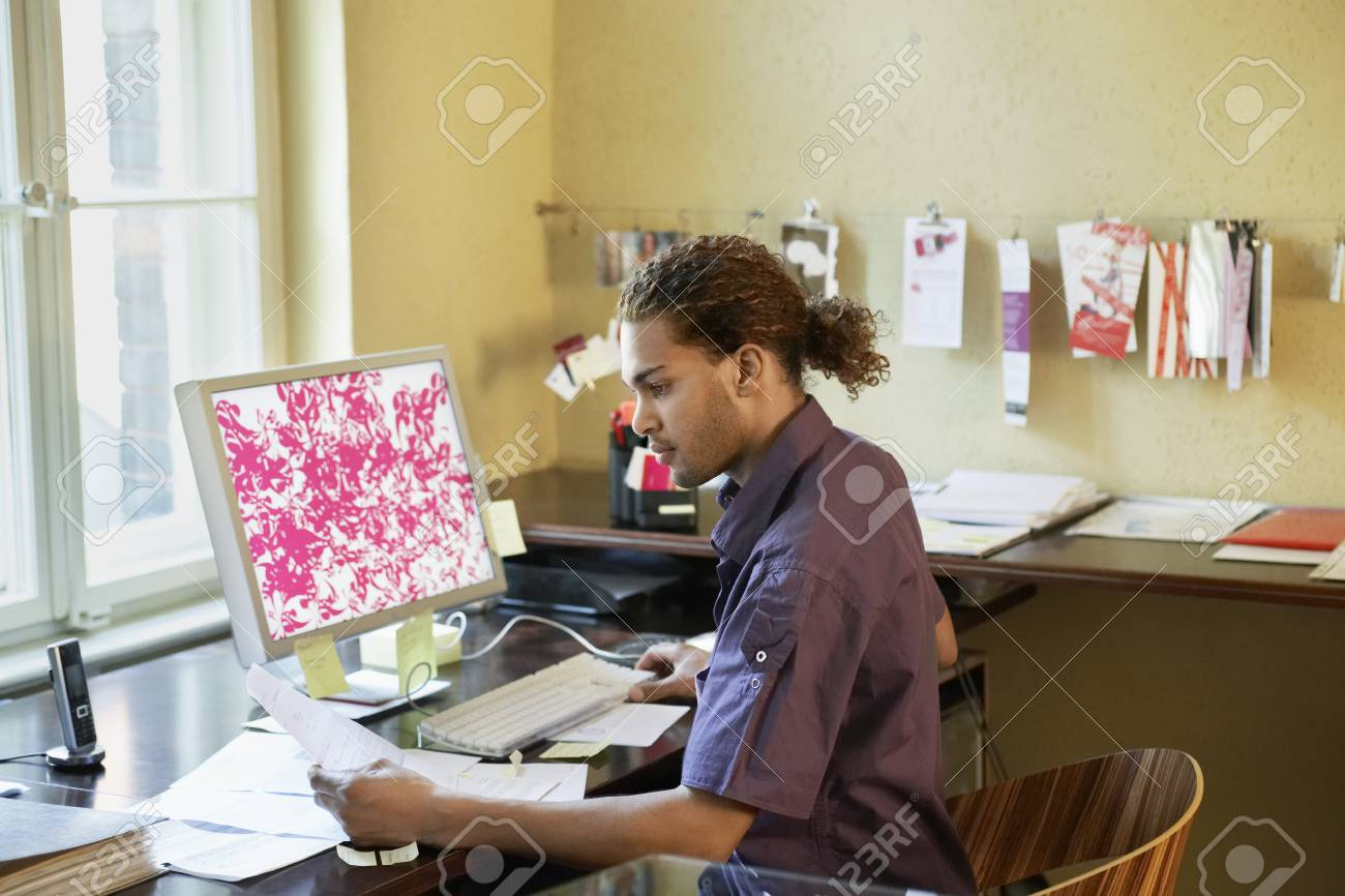 Young man reading papers near computer in office Stock Photo - 19076750