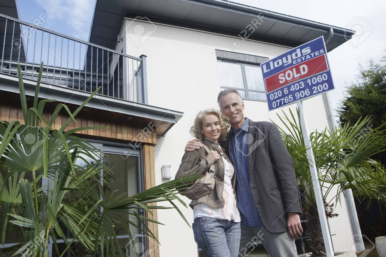 Couple embracing outside new home with sold sign portrait Stock Photo - 19077316