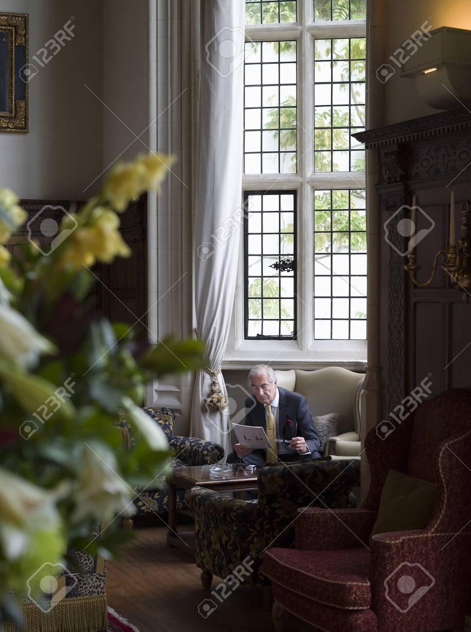 Senior man reading in interior with antique furniture Stock Photo - 19077712