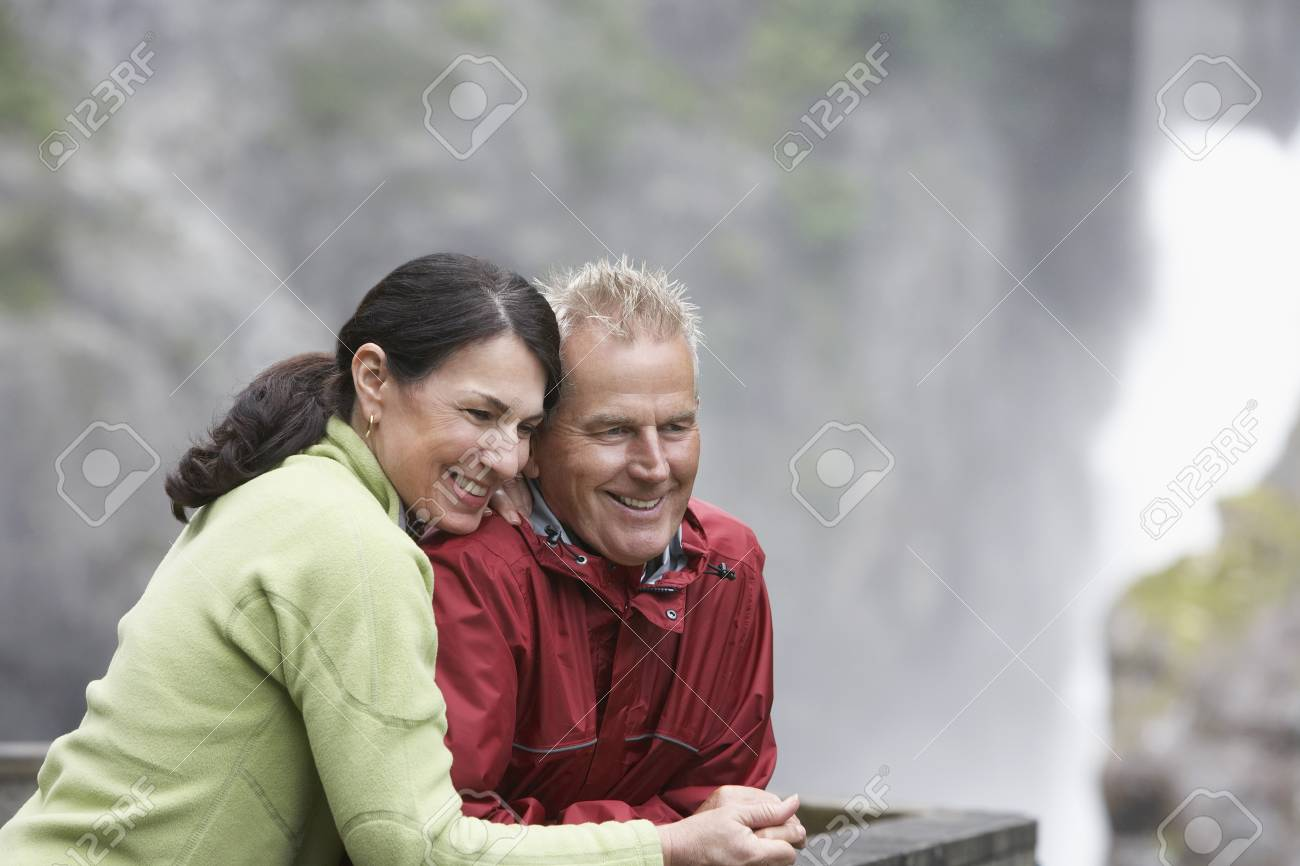 Man and woman in mountains looking down smiling Stock Photo - 19078101