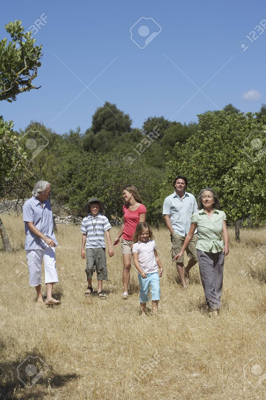 Three-generation family with two children (6-11) walking in field Stock Photo - 19078348