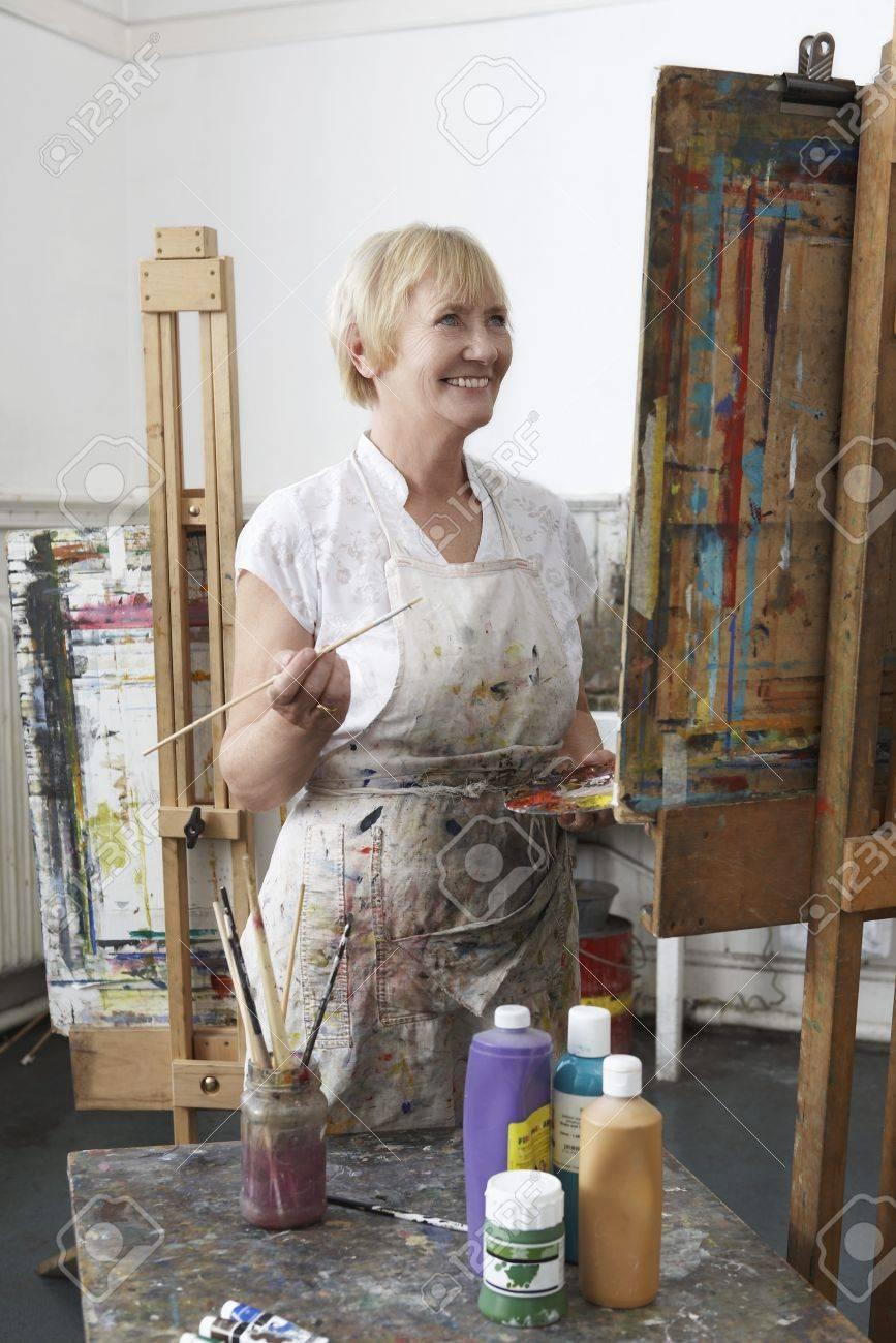 Mature female artist painting at easel in art studiocanvas in studio Stock Photo - 19078553