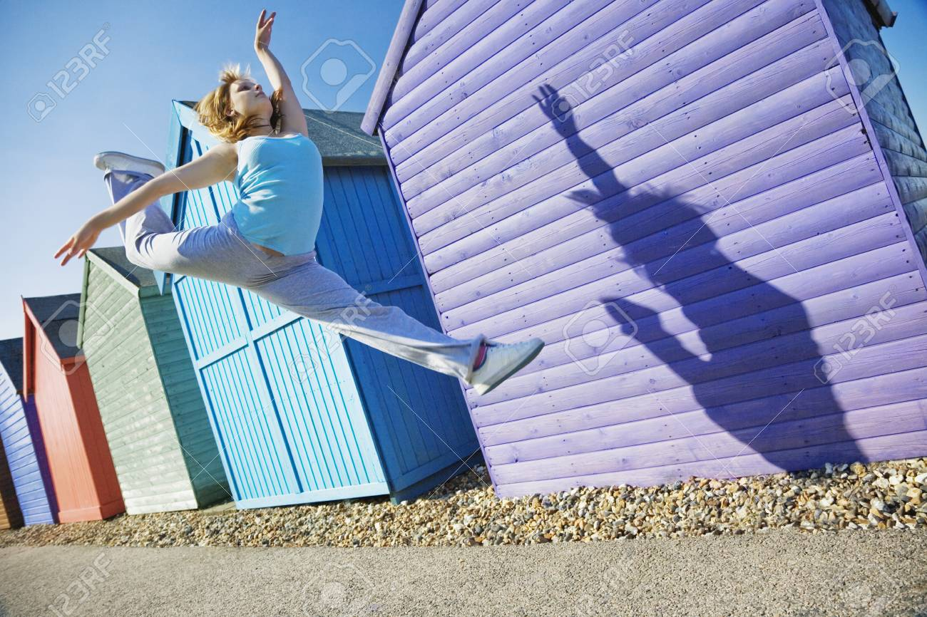 Woman jumping in front of beach huts Stock Photo - 19078939