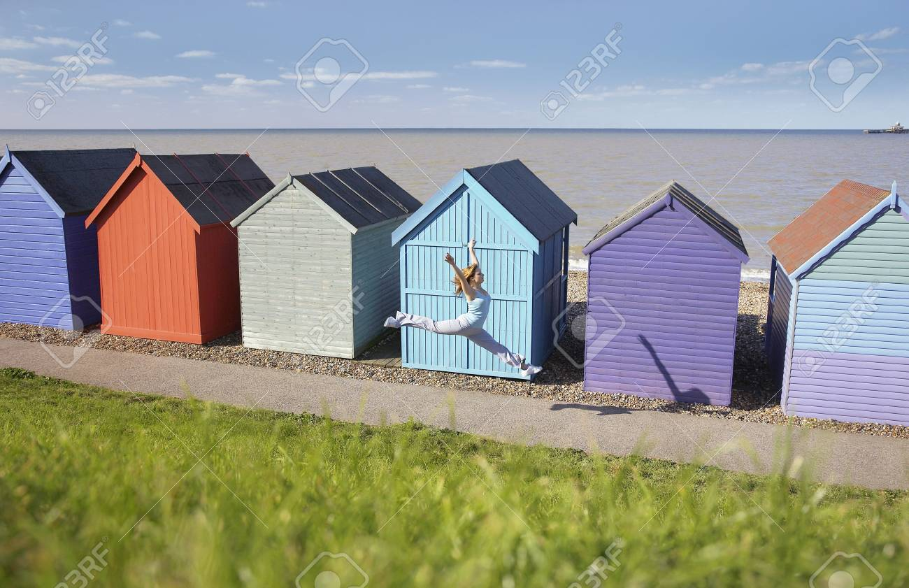 Woman jumping in front of beach hut Stock Photo - 19078943