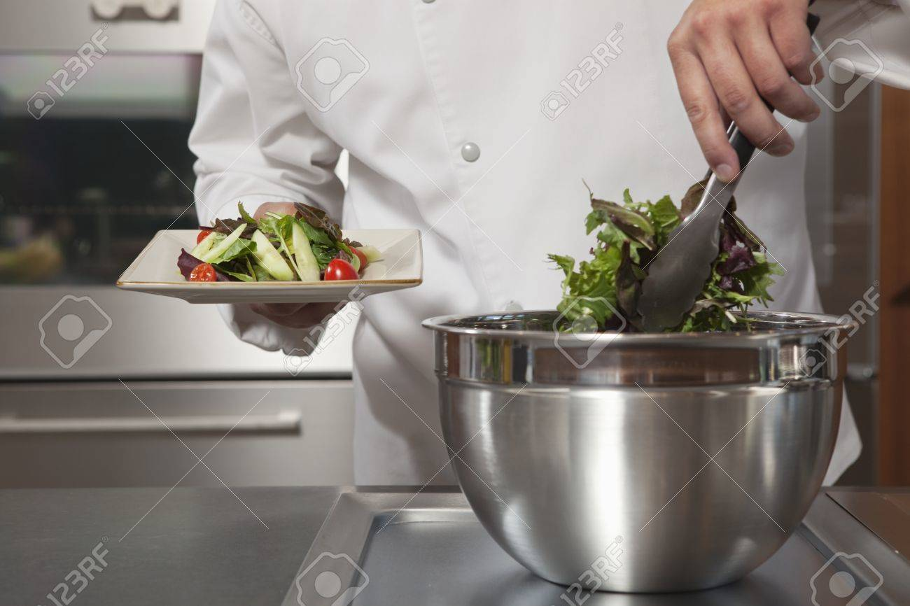 Mid- adult chef lifts leaf vegetables onto side plate Stock Photo - 20741380