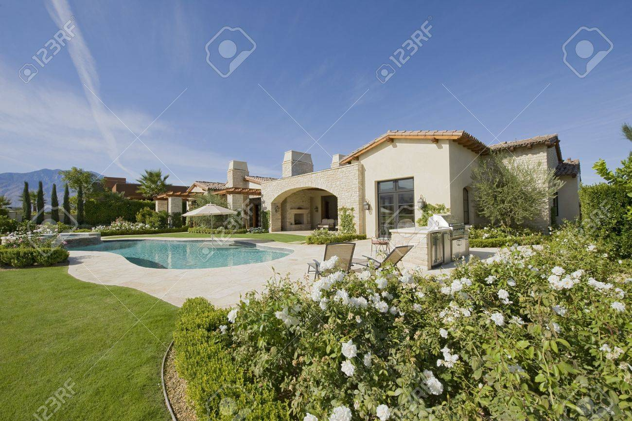 House exterior in daylight with a garden  plants  a swimming pool and hills in the far distance Stock Photo - 20741846