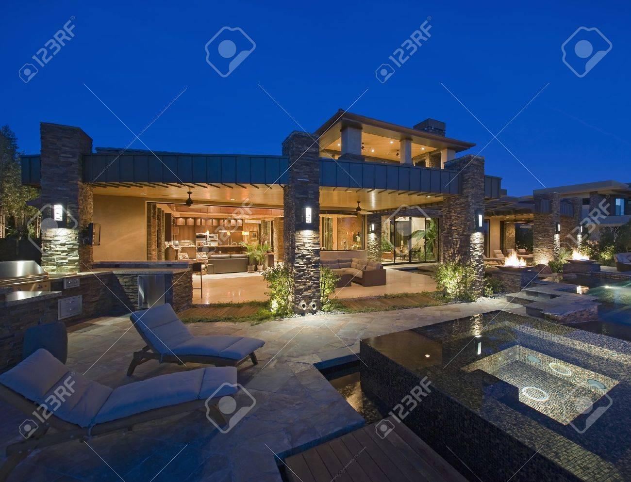 Exterior De La Casa Iluminada Por La Noche Con Muebles De Jardín ...