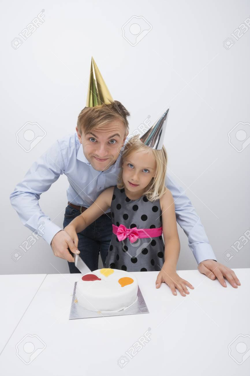 Portrait of father and daughter cutting birthday cake at table Stock Photo - 25294568