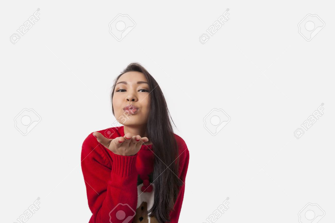 Portrait Of Woman In Christmas Sweater Blowing Kiss Over Gray ...