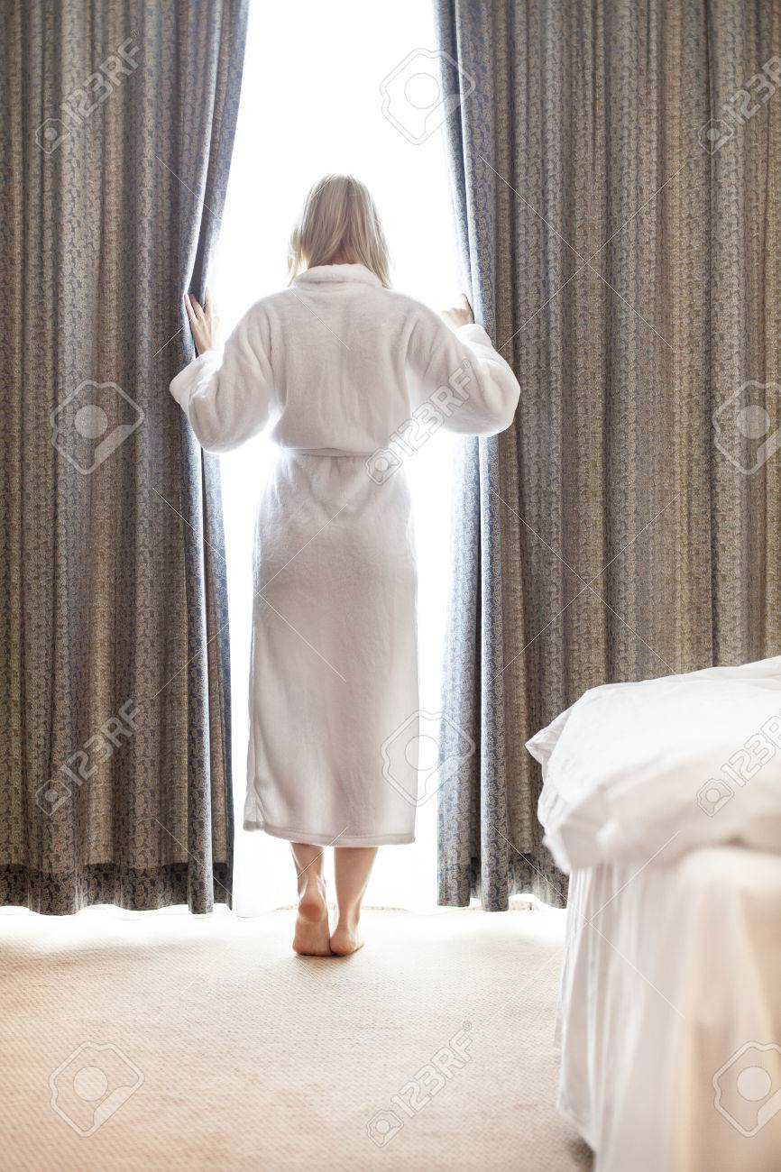 Full length of young woman in bathrobe opening bedroom curtains..