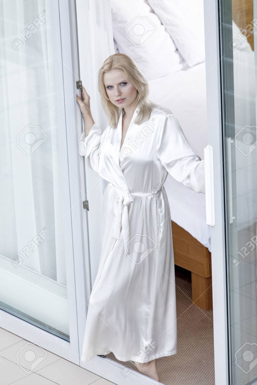 88208b4673 Foto de archivo - Retrato de una mujer joven hermosa en bata de baño de pie  en el balcón puerta