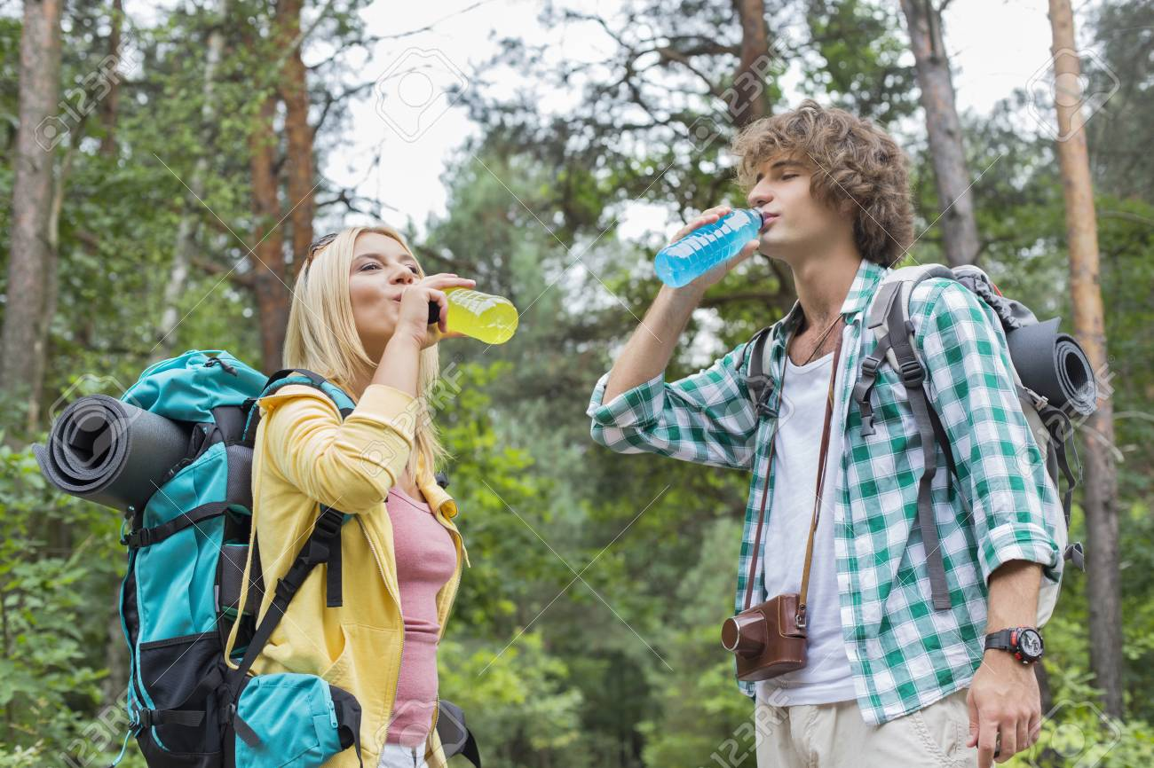 Young hiking couple drinking energy drinks in forest - 33862004