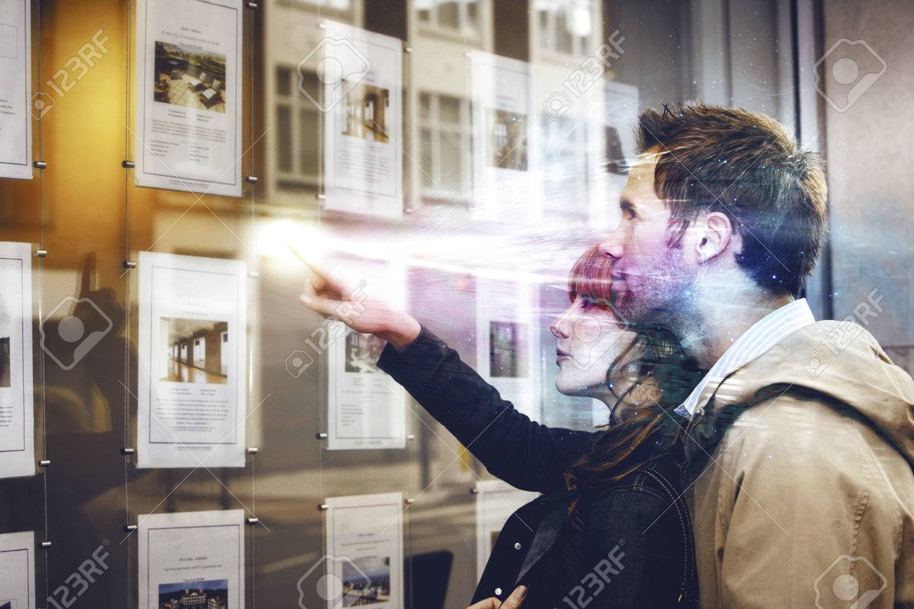 Side view of a young couple looking at window display at real estate office - 32901028