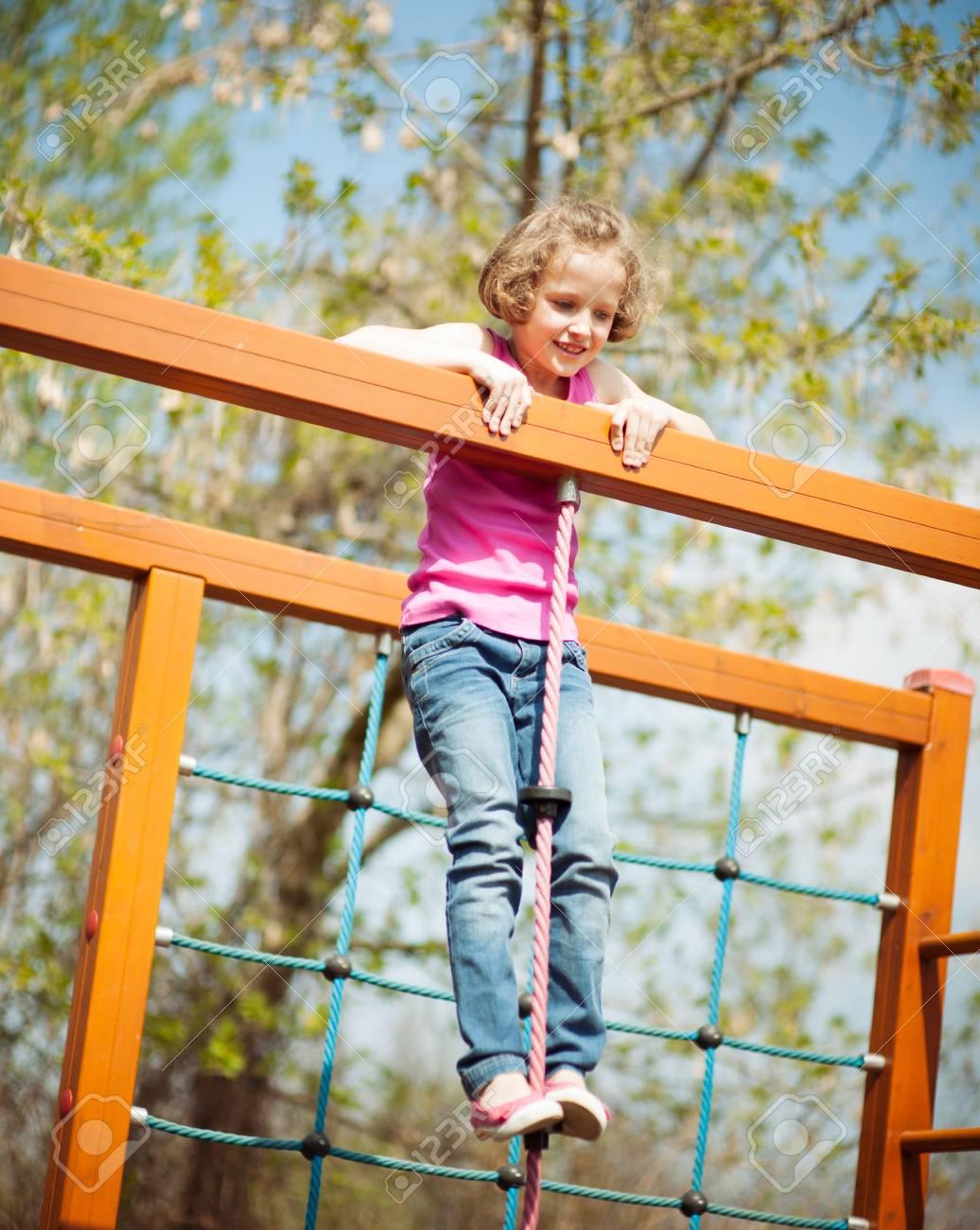 Junges Mädchen Steht Oben Am Seil Und Klettergerüst Lizenzfreie ...