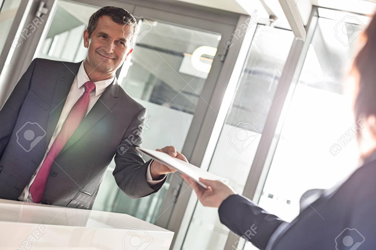 Homme d affaires recevant le document de la réceptionniste au