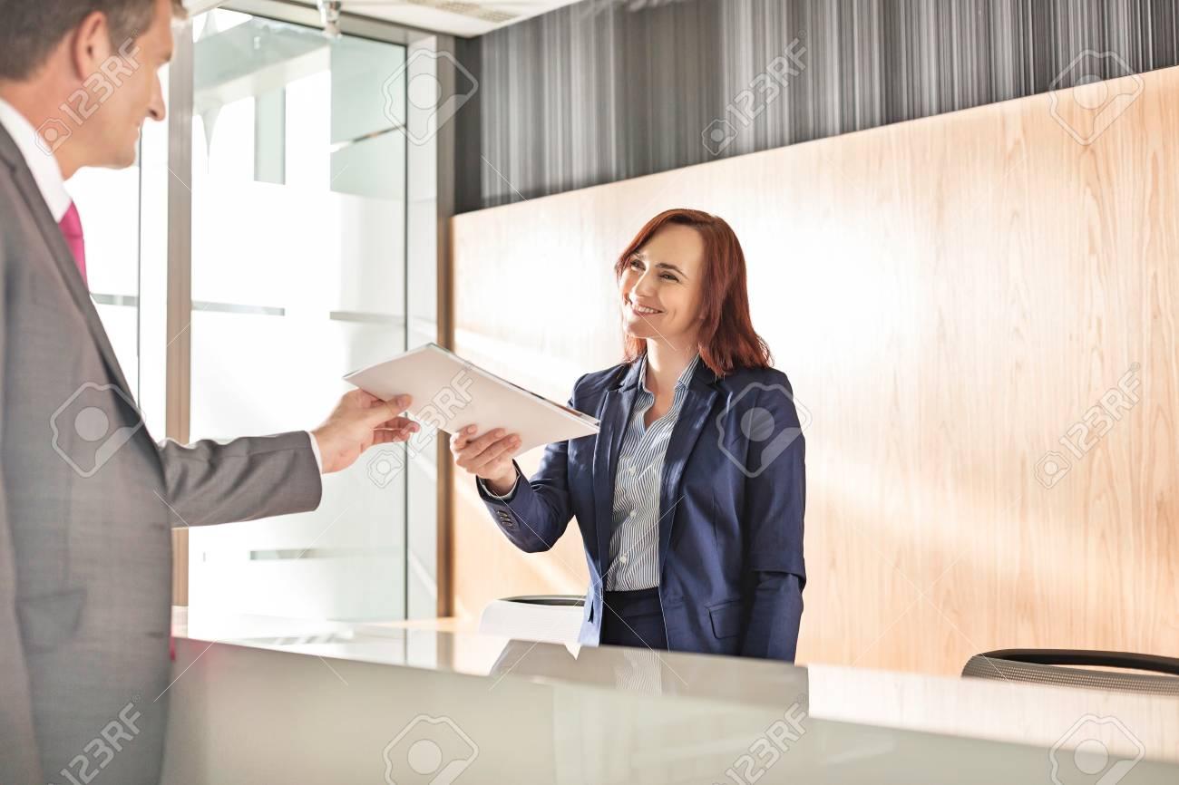 Homme daffaires recevant le document de la réceptionniste au bureau