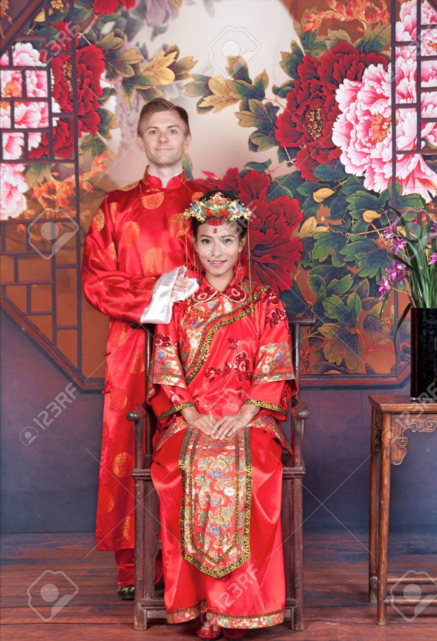 784563127 Mixed Race Bride and Groom in Studio wearing traditional Chinese wedding  outfits Stock Photo - 76803501
