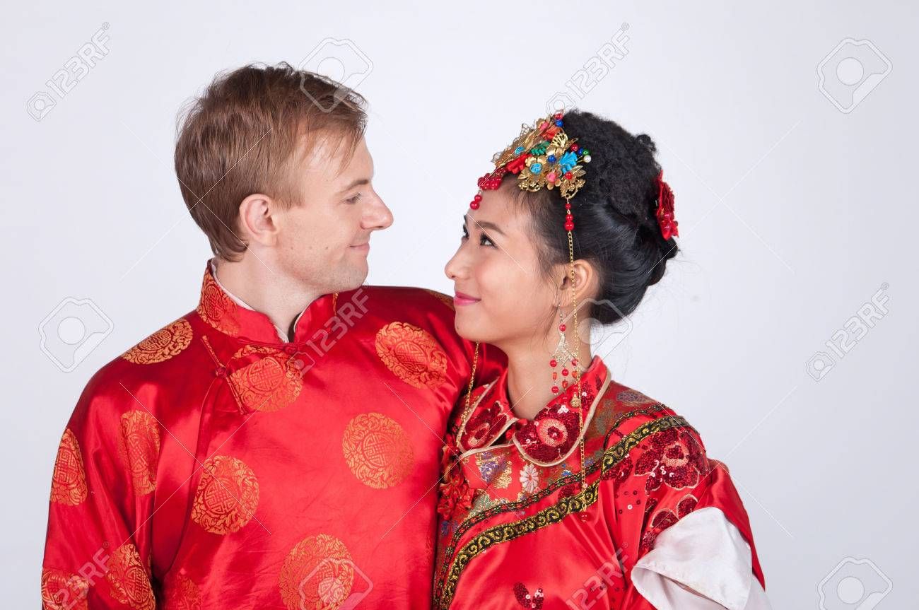 c9618df91 Mixed Race Bride and Groom in Studio wearing traditional Chinese wedding  outfits Stock Photo - 76803845