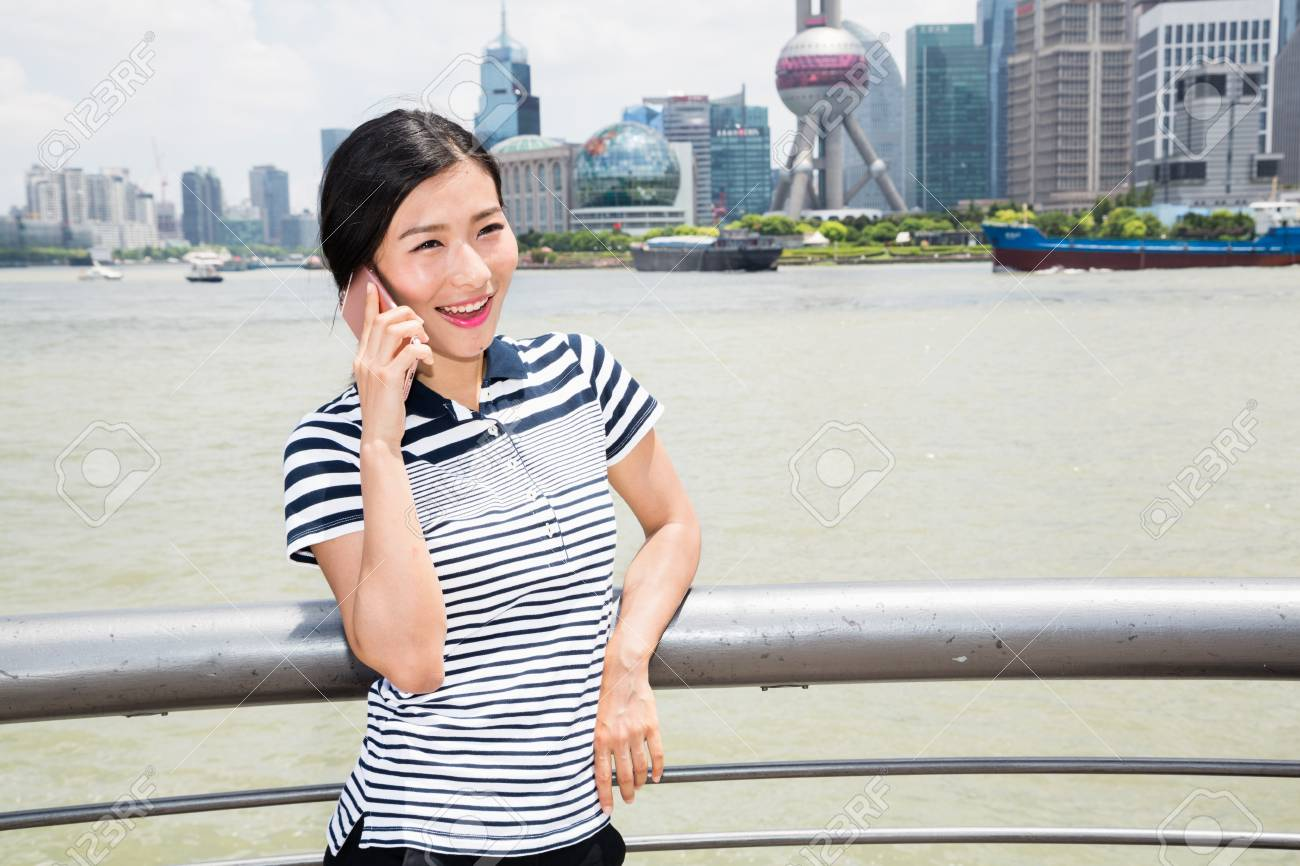 happy young woman using smart phone while leaning on railing stock