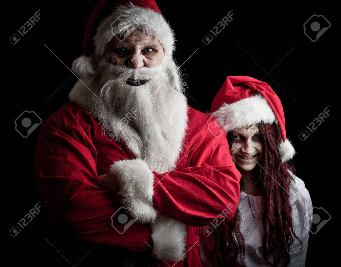 portrait of a scary looking santa claus and an elf stock photo